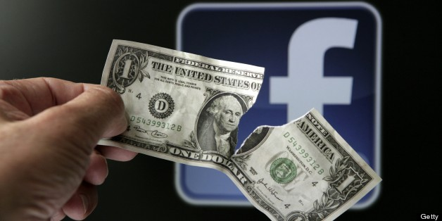 """GERMANY - MAY 23: Torn dollar bill in front of the Facebook logo, symbol picture: """"The downward trend continues"""" - big losses for investors of Facebook shares. (Photo by Ulrich Baumgarten via Getty Images)"""