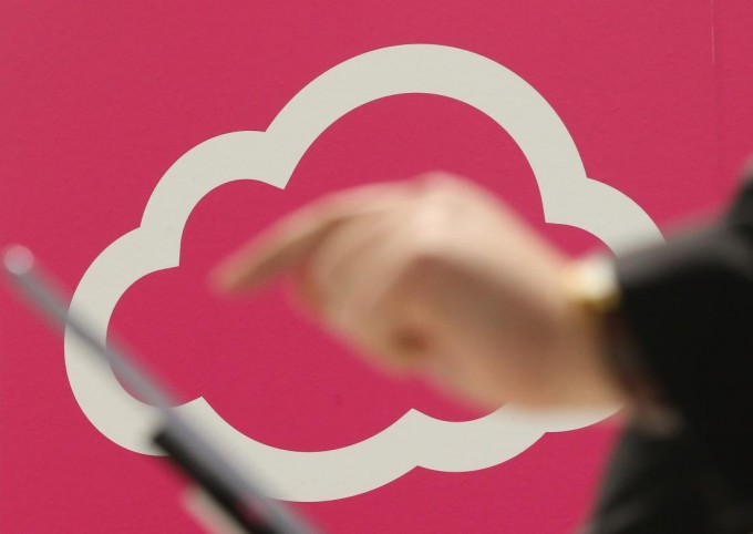 HANOVER, GERMANY - MARCH 05:  A visitor tries out a tablet computer next to a cloud computing and technology symbol at the Deutsche Telekom stand at the 2013 CeBIT technology trade fair on March 5, 2013 in Hanover, Germany. CeBIT will be open March 5-9.  (Photo by Sean Gallup/Getty Images)