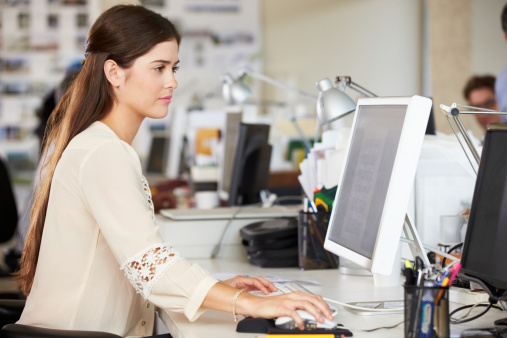 Woman Working At Desk In Creative Office